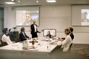 Mature businesswoman giving presentation to colleagues in board room during global conference meeting at office (image)